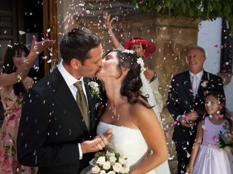 Guests throwing confetti over kissing bride and groom, outdoors