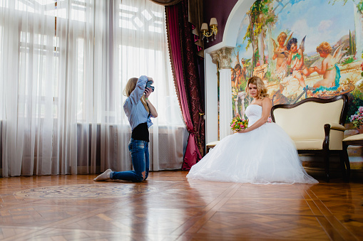 Wedding photographer is taking pictures the bride in the studio
