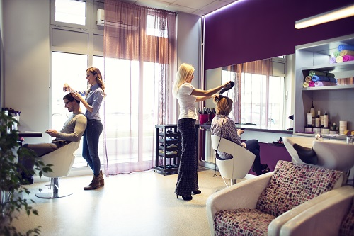Female hairdressers working in hair salon.
