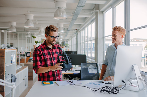 Young developers testing virtual reality glasses in office