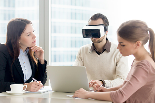 Businessman wearing vr headset for laptop at business meeting. Virtual development business team working on augmented reality improvement, future computer technology for business concept