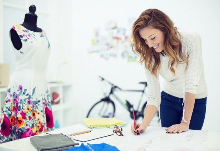 Young Cheerful Woman, small business owner, fashion designer/dressmaker working at office. Sketching her new ideas. Selective focus to her face, shallow DOF. *Dress has been bought at C&A and they do not have copyrighted or protected cloth.