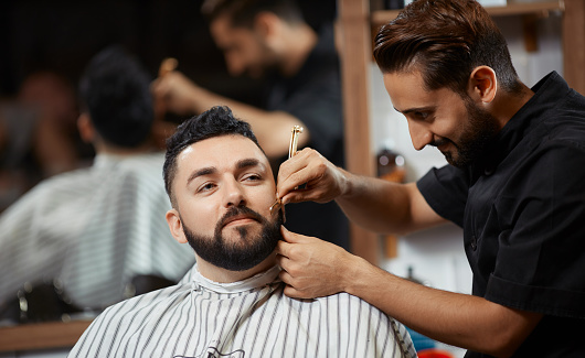 Hairdresser cutting bread for client with razor at modern barbershop