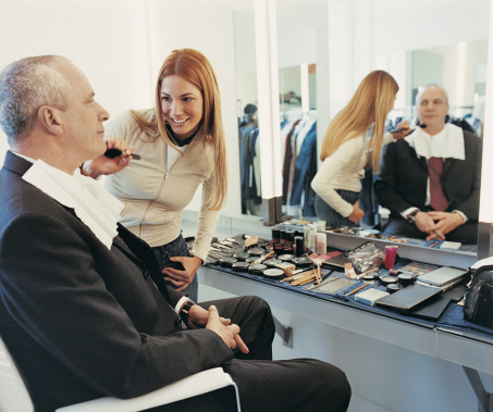 TV Presenter Receiving a Brushing of Foundation From a Makeup Artist in the Dressing Room of a TV Studio
